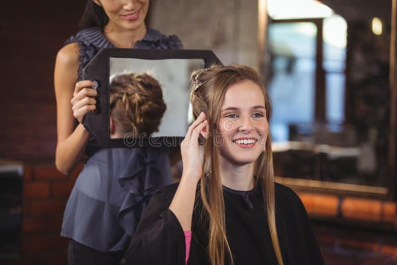 Kapper die vrouw haar kapsel in spiegel tonen royalty-vrije stock afbeeldingen