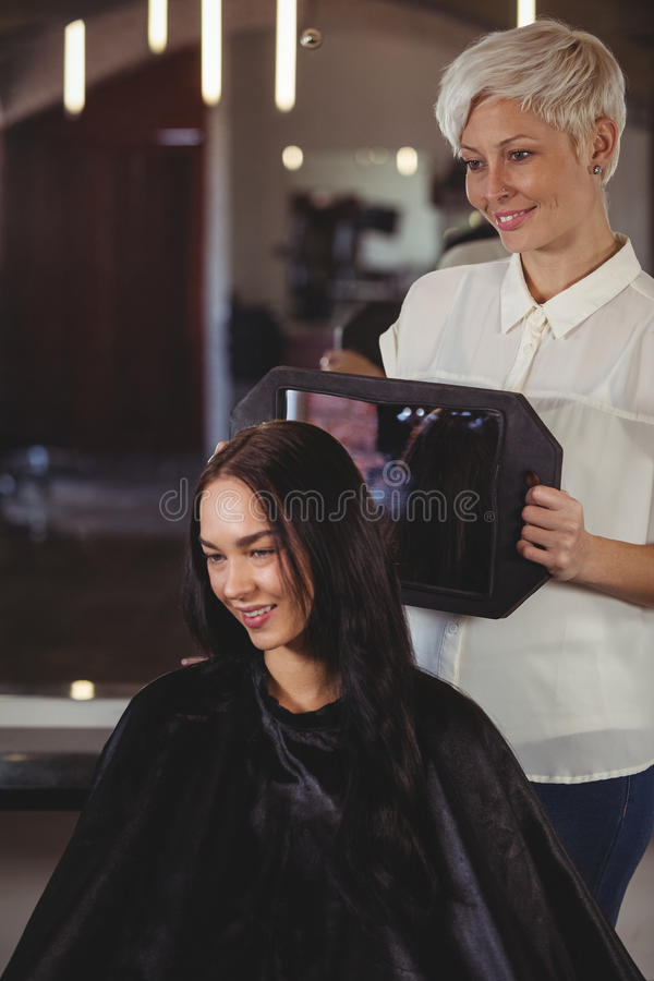 Kapper die vrouw haar kapsel in spiegel tonen royalty-vrije stock foto's
