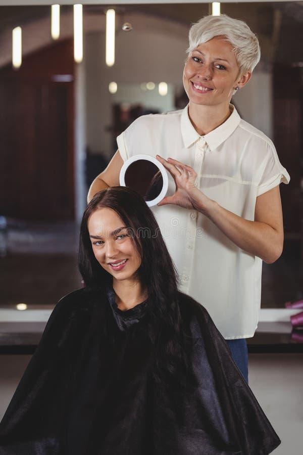 Kapper die vrouw haar kapsel in spiegel tonen stock fotografie