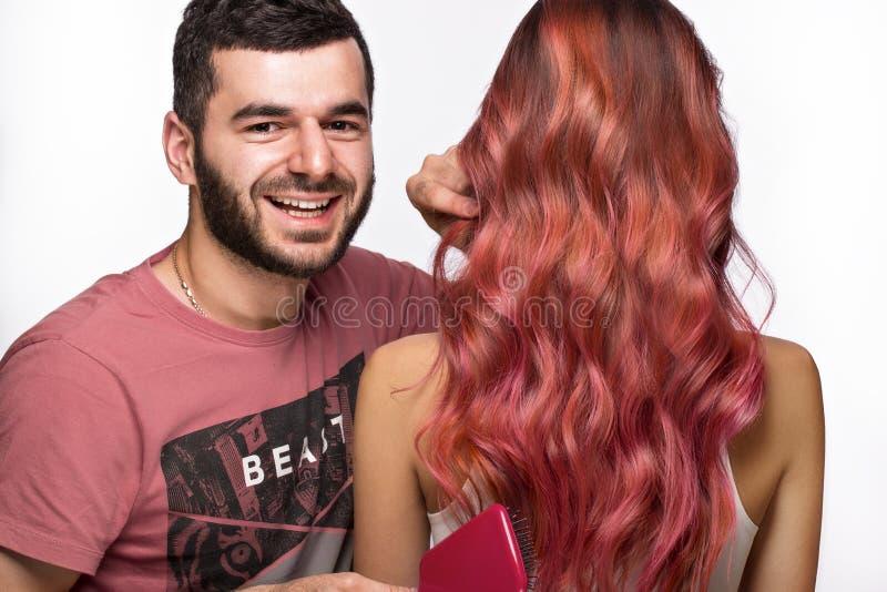 Kapper en mooi roze-haired meisje met een volkomen vlot haar en een klassieke samenstelling Het Gezicht van de schoonheid royalty-vrije stock fotografie