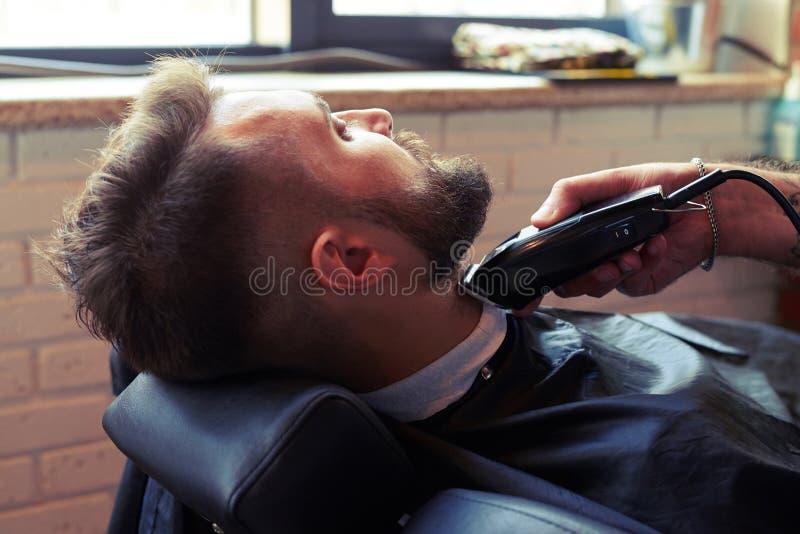 kapper het scheren baard met scheerapparaat stock foto