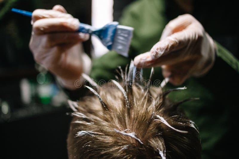 Kapper met een borstel om haarverf toe te passen Het kleuren in de kapperswinkel royalty-vrije stock afbeeldingen