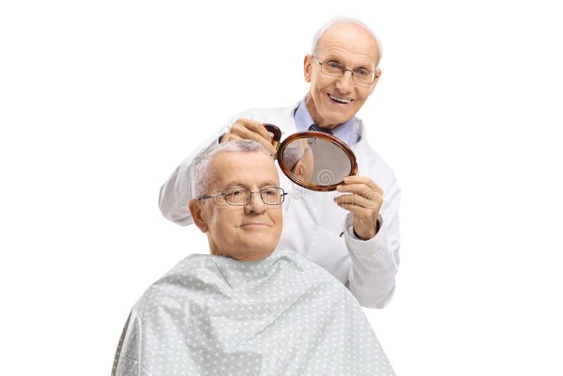 Kapper met een spiegel die een rijpe mens zijn nieuw kapsel tonen royalty-vrije stock afbeeldingen