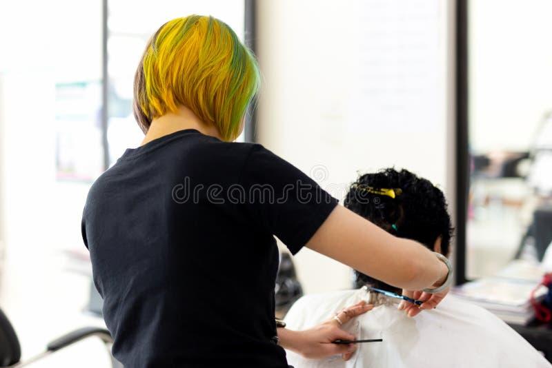 Kapper met stijl die van het manier de kleurrijke haar oude dame in salon snijden royalty-vrije stock afbeeldingen