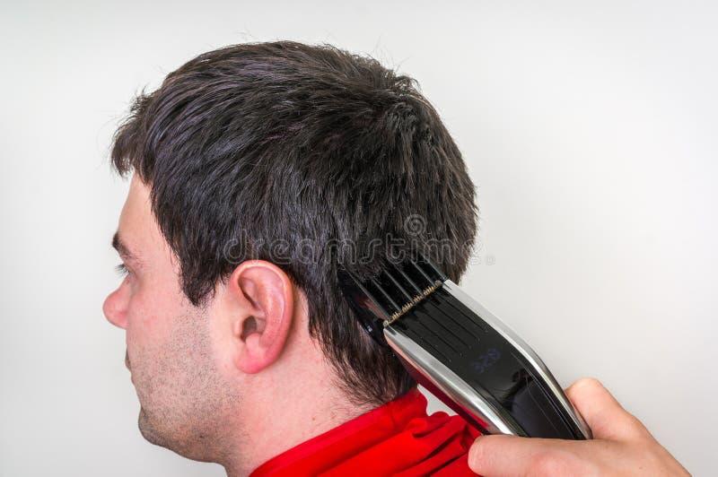 Kapper scherp haar met elektrische haarclipper in sh kapper royalty-vrije stock fotografie