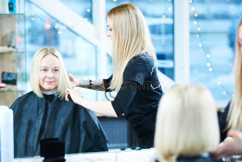 Kapper of stilist op het werk Haar van de kapper het scherpe vrouw stock afbeeldingen