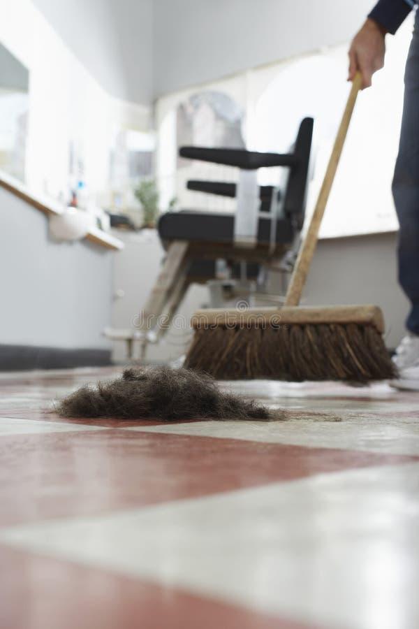 Kapper Sweeping Hair Clippings op Vloer stock fotografie