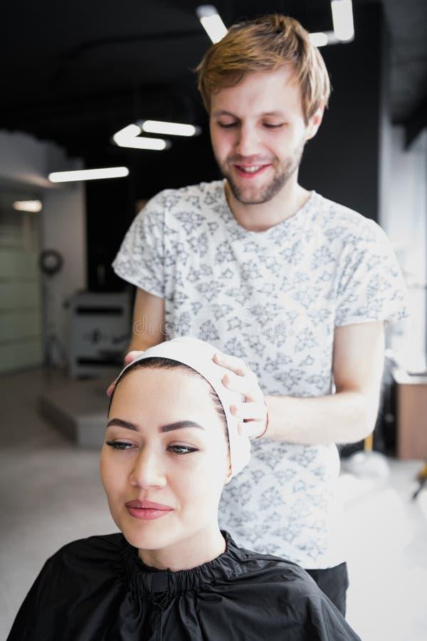 Kapper verpakkende handdoek op klanten` s hoofd Donkerbruine vrouw die haarbehandeling in een salon krijgen stock afbeelding