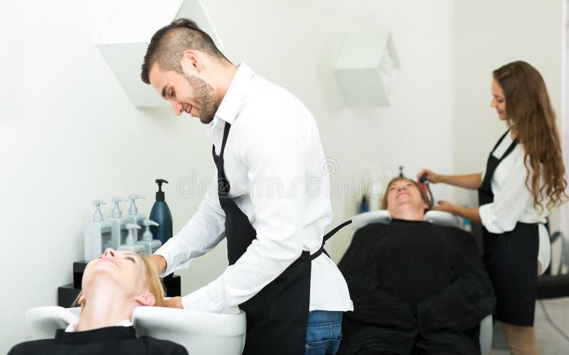 Kappers die haar wassen aan klanten stock fotografie