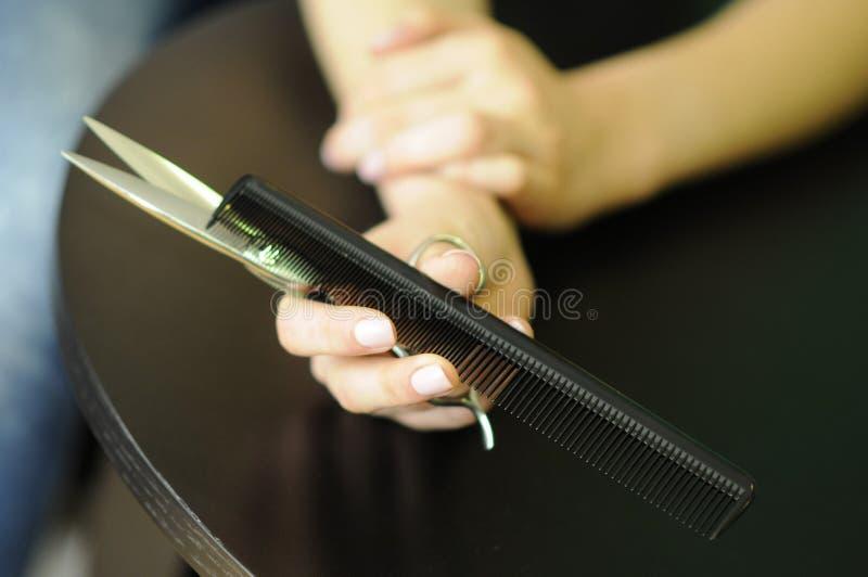 Kappershulpmiddelen in de handen van een professionele, lange haar, een schaar en een kam in zijn handkapper stock foto