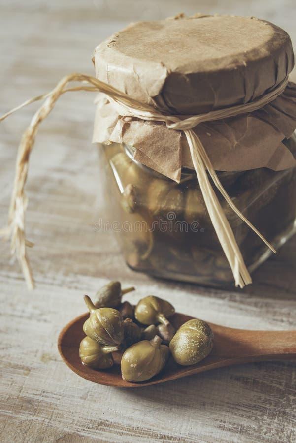 Kappertjes in een houten lepel stock foto's