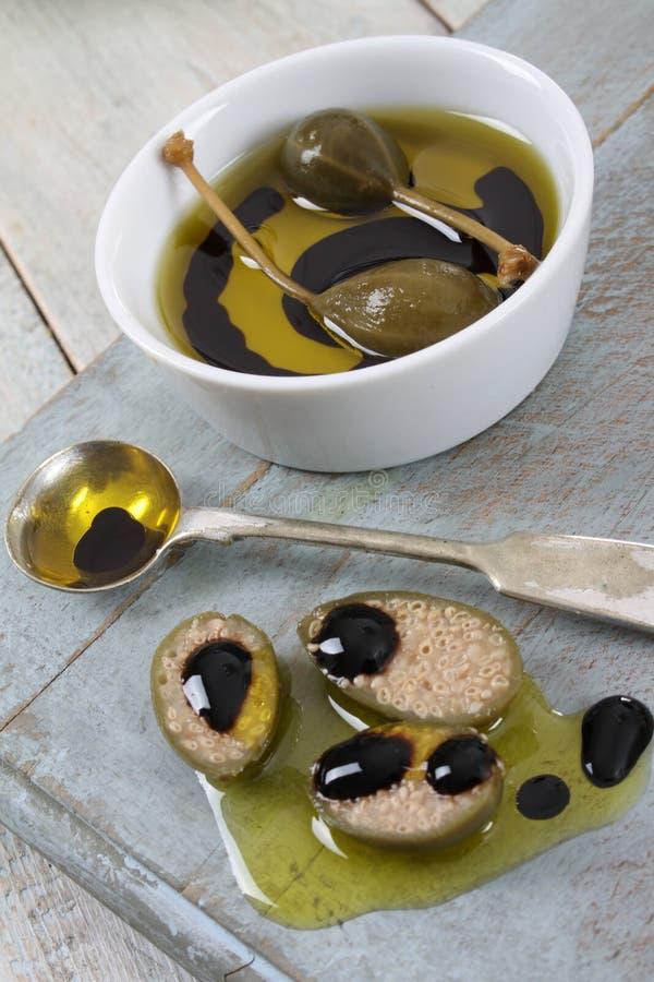 Kappertjesbessen met olijfolie en balsemiek royalty-vrije stock afbeelding