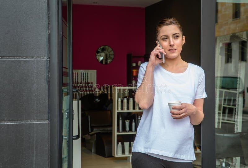 Kappervrouw die met smartphone in een koffiepauze spreken royalty-vrije stock fotografie