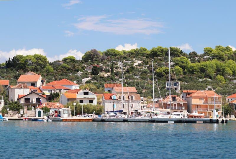 Kaprije, Croacia, Europa - 7 9 2018: Terraplén de una pequeña ciudad croata en el mar adriático Navegación del yate en el fondo d fotografía de archivo libre de regalías