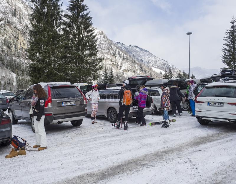 KAPRUN, ÁUSTRIA, o 12 de março de 2019: Os esquiadores estão saindo dos carros no lugar de estacionamento na estância de esqui de imagens de stock