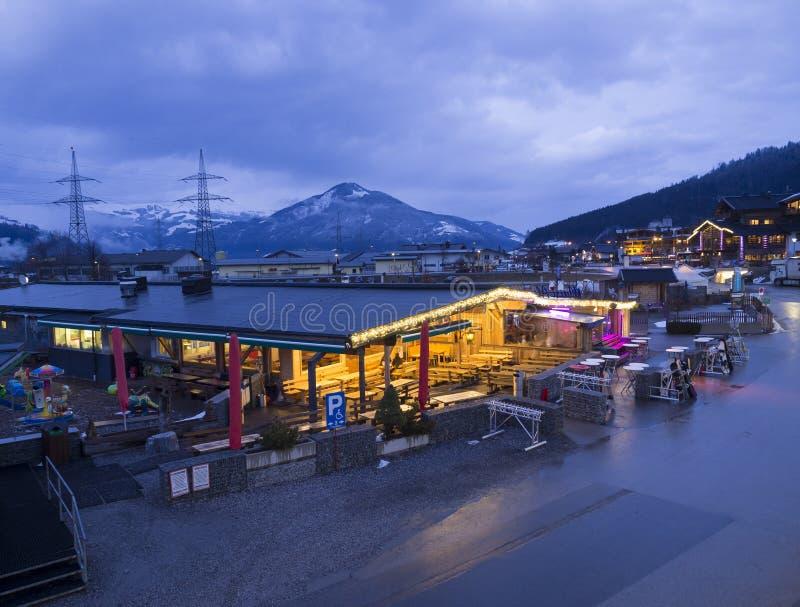 KAPRUN, ÖSTERREICH, am 13. März 2019: Ansicht Nigt im Freien über belichtetes Kaprun nahe bei Kabelstation mit Apres-Skirestauran stockfotografie
