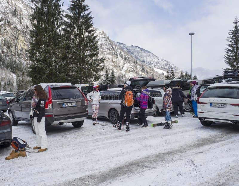 KAPRUN, ÖSTERREICH, am 12. März 2019: Skifahrer gehen von den Autos am Parkplatz an Kitzsteinhorn-Skiort hinaus und machen stockbilder