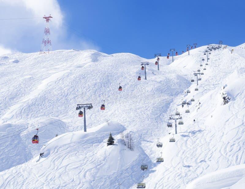 KAPRUN, AUSTRIA, Marzec 12, 2019: Śnieg zakrywał skłony z czerwonymi wagonami kolei linowej i krzeseł dźwignięciami z bezpłatnymi obrazy stock