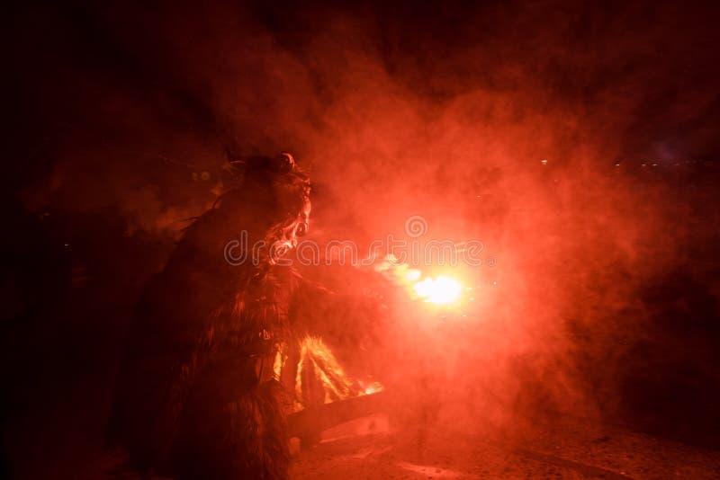 Kaprun, Salzburg/Austria - 5 grudnia 2019 r.: Krampus z ogniem i czerwonym dymem na tradycyjnym publicznym show Krampuslauf w Kap obrazy stock