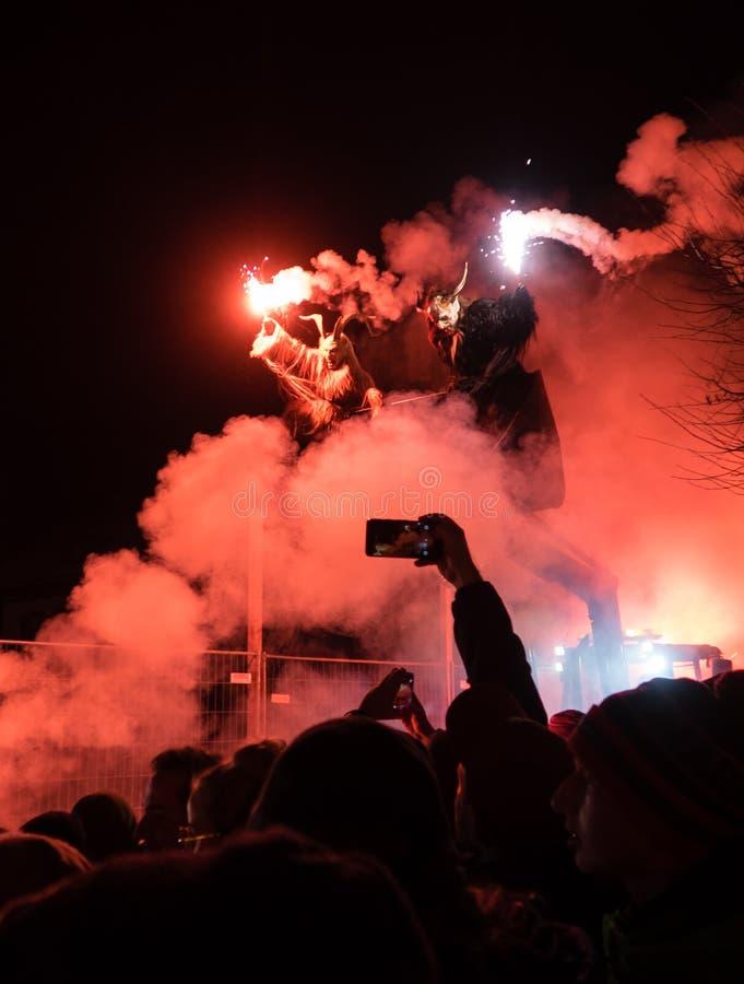 Kaprun, Salzburg/Austria - 5 grudnia 2019 r.: Krampus z ogniem i czerwonym dymem na traktorze w tradycyjnym pokazie publicznym Kr obraz stock