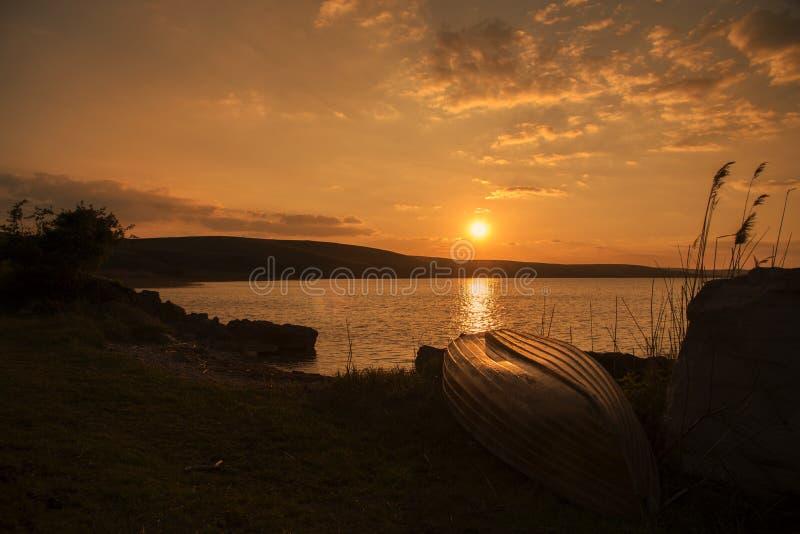 Kapsejsat fartyg på kusten av Razelm sjön, i solnedgång arkivfoto