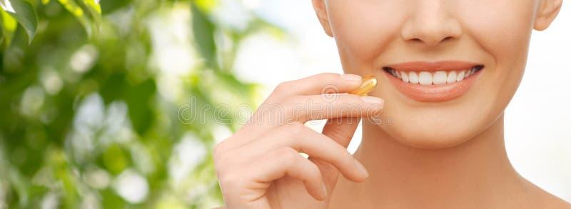Kapsel för vitaminer för omega 3 för härlig kvinna hållande arkivfoton