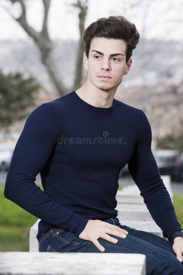 Kapsel leuke jonge mens - Openlucht met blauwe lang-sleeved royalty-vrije stock afbeelding