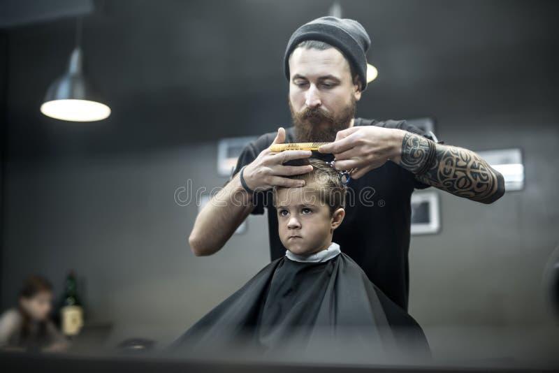 Kapsel van kleine jongen in herenkapper stock foto