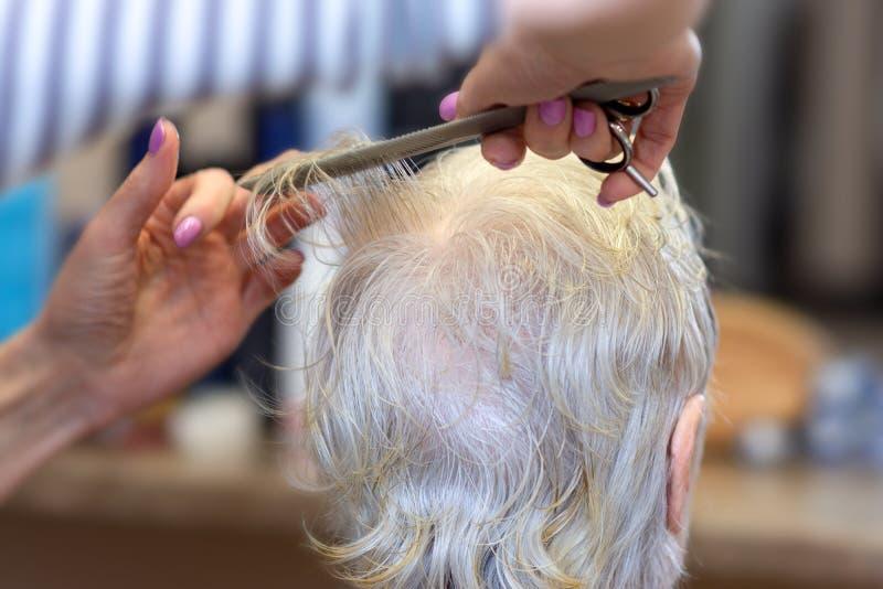 Kapsel voor de bejaarden Het proces om het haar van de oma in de Kapperswinkel te snijden Het concept leeftijd stock foto's