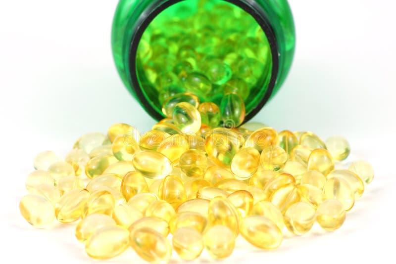 Kapseln des Vitamins D-3 mit grüner Pilleflasche stockfotos