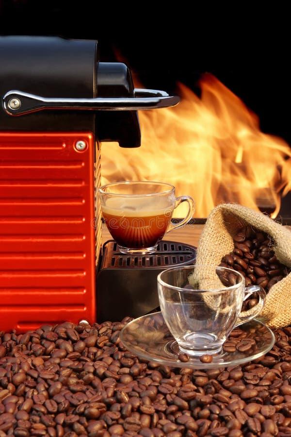 Kapseln Sie Kaffeemaschine mit zwei Espressoschalen nahe Kamin ein stockfotos
