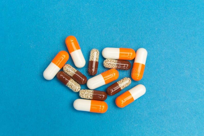 Kapseln u. x28; pills& x29; auf einem blauen Hintergrund Medizinischer Hintergrund, Schablone lizenzfreie stockfotos