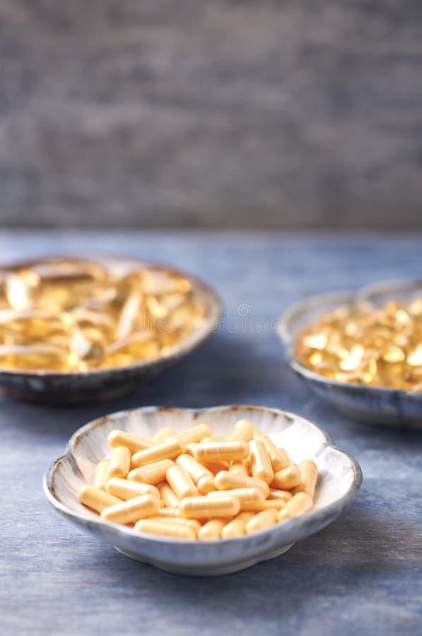 Kapslar för Coenzyme Q10, för omega 3 och för vitamin E dietary supplements arkivbilder
