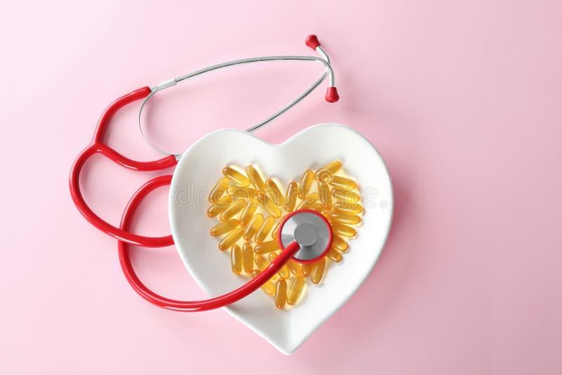 Kapslar för fiskolja i hjärta formade plattan med stetoskopet royaltyfria bilder