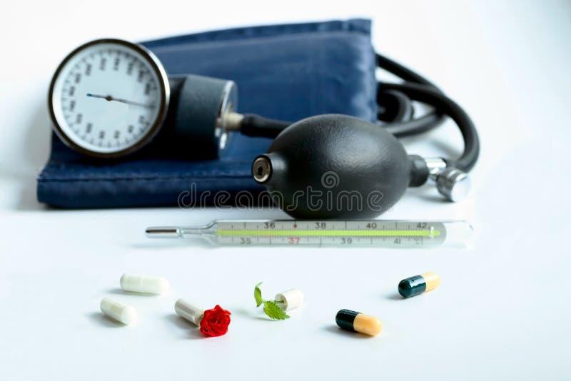 Kapslar med drogen är på bakgrunden av en termometer och en apparat för att mäta blodtryck Från den öppnade kapseln royaltyfri foto