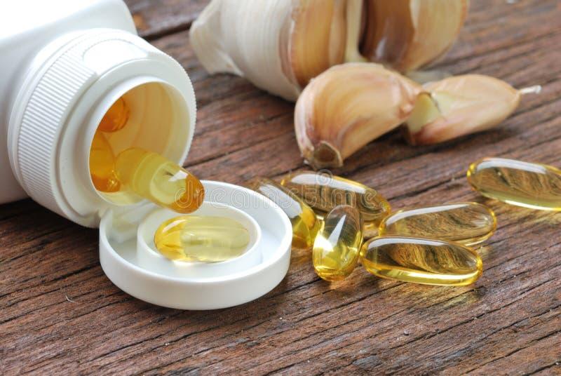 Kapslar/preventivpillerar för vitlök olje- arkivbilder