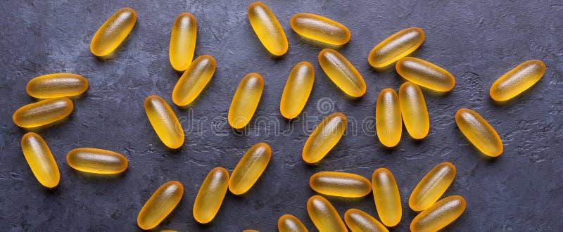 Kapsuły omega 3 na zmroku kamienia tle Zamkniętym w górę opieki zdrowotnej pojęcia fotografia stock