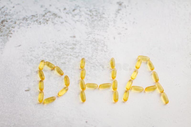 Kapsuły rozkładać w postaci listów DHA Zamyka w górę złocistych kapsuł omega-3 zdjęcia royalty free