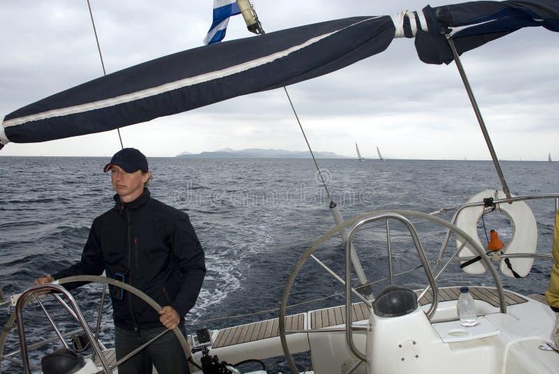 Kaptenen kontrollerar yachten. royaltyfria bilder