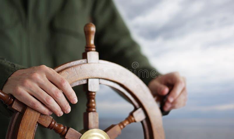 Kapteninnehavhand på skepprodern royaltyfri bild