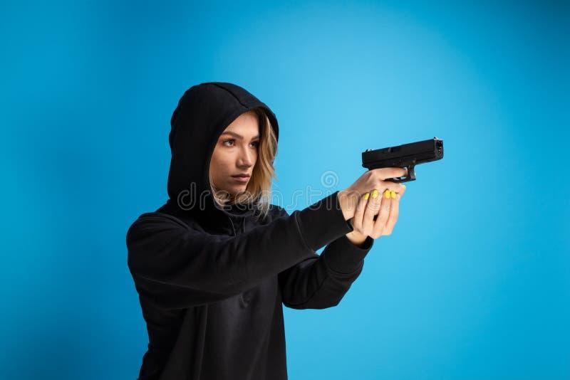 Kapturzasta dziewczyna trzyma pistolet wskazujący prawa strona zdjęcia royalty free