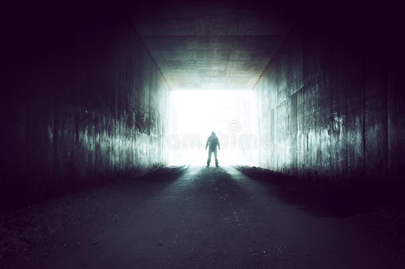 Kapturzasta sylwetkowa postaci pozycja na krawędzi tunelowy przyglądającego out na jaskrawym przeeksponowywającym świetle obrazy stock