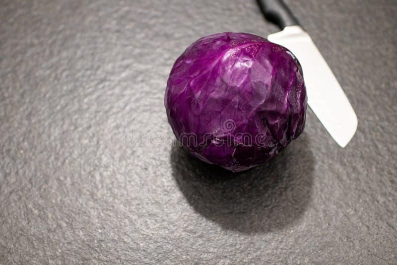 kapuściana czerwona piłka z kuchennym nożem na czarnym granitu stole obrazy stock