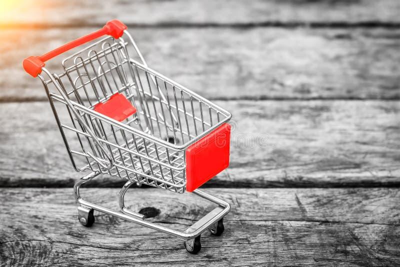 Kar van de kruidenierswinkelopslag op de oude houten achtergrond Leeg het winkelen karretje Commerciële ideeën en detailhandel stock foto's