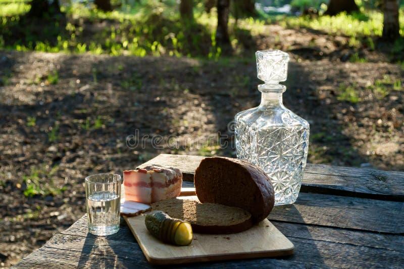 Karaf met wodka en snack op een bosopen plek stock afbeeldingen