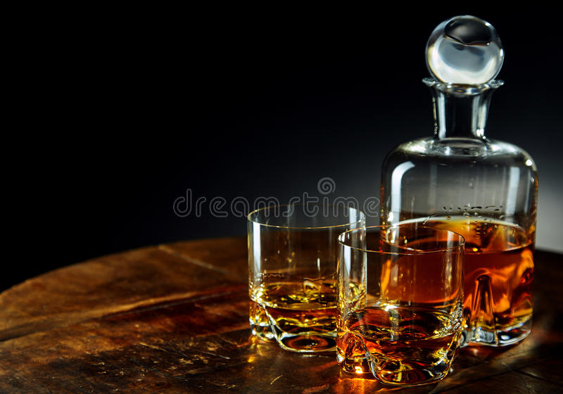Karaf whisky naast twee half gevulde glazen stock fotografie