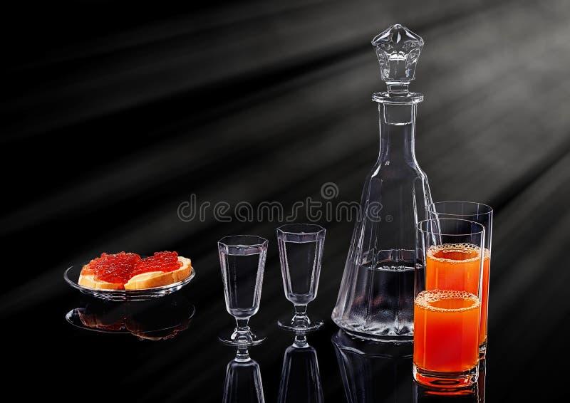 Karaff och två skottexponeringsglas med isvodka, två röda kaviarsmörgåsar för lax på en glass platta och två exponeringsglas med arkivbilder