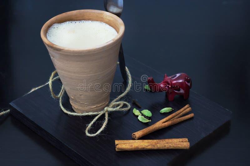 Karak indio del té de chai del masala con las especias y la leche, en vidrio de la arcilla Fondo de madera negro imagen de archivo libre de regalías