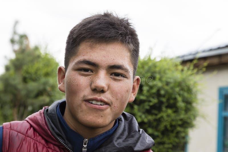 Karakol, Kyrgystan, el 13 de agosto de 2018: Retrato de un kirguizio joven apuesto en el mercado animal semanal de domingo en la  fotografía de archivo