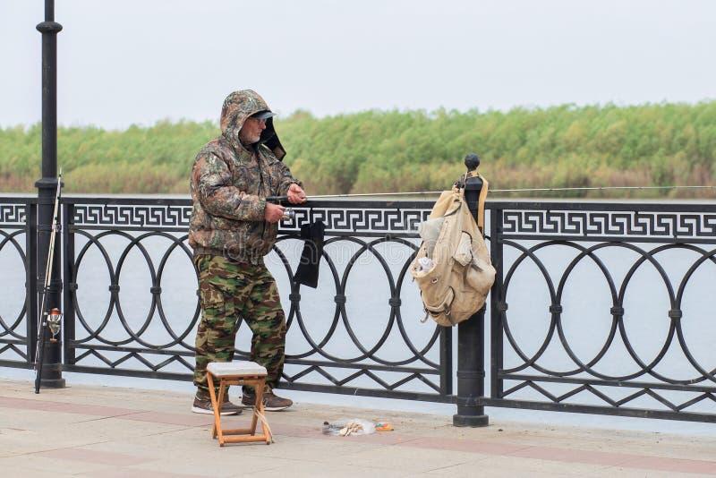 Karaku?owy, Rosja, 05 01 2019: Męski rybak w ochronnego kostiumu chwytów rybie fotografia royalty free